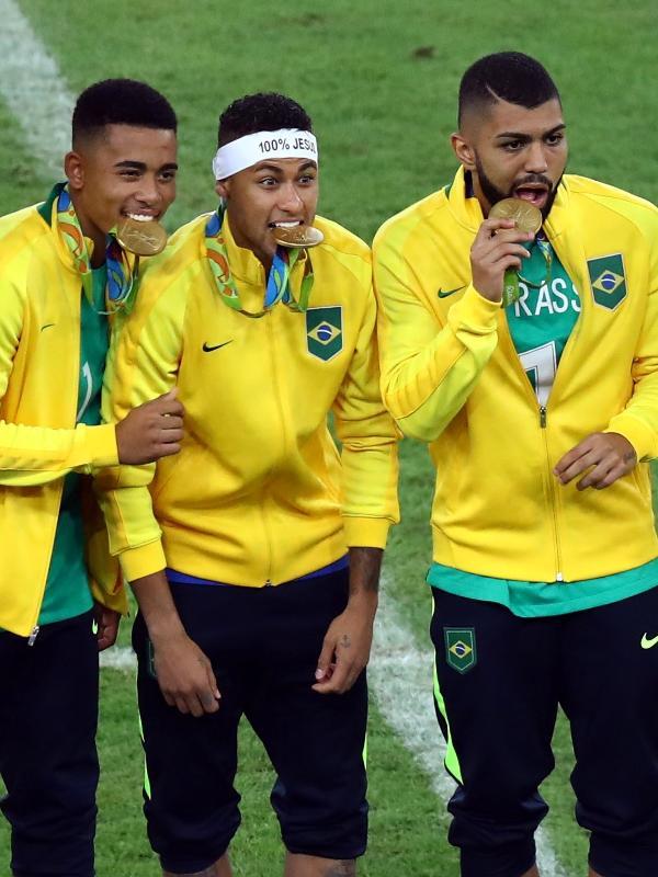 Brasileiros exibem a medalha de ouro conquistada no futebol após vitória sobre a Alemanha