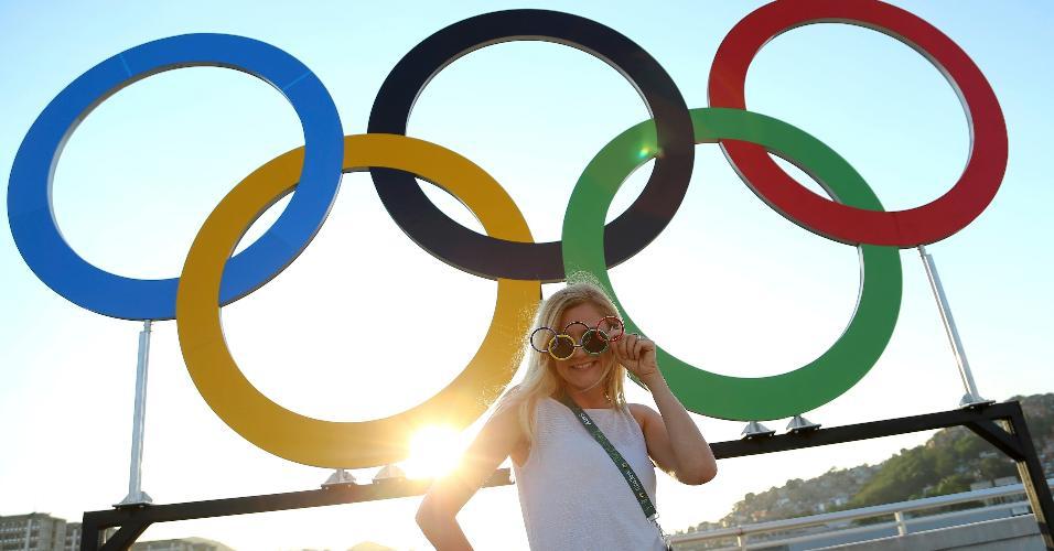 Torcedora posa para foto ao lado dos arcos olímpicos antes do início da cerimônia de abertura