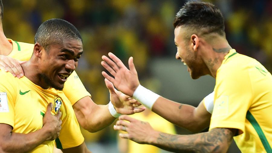 Douglas Costa e Neymar em ação durante jogo da seleção brasileira - Christophe Simon/AFP