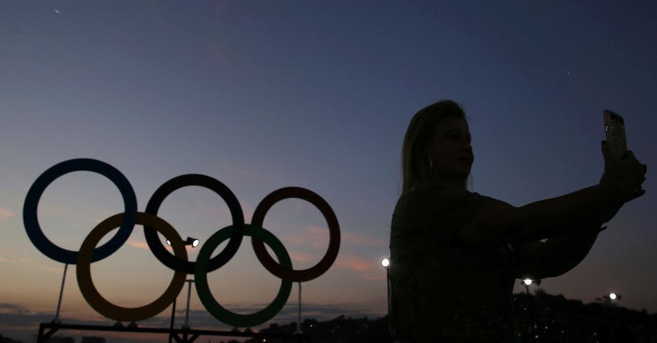 Festival de selfies na abertura: torcedora tira foto próxima aos arcos olímpicos