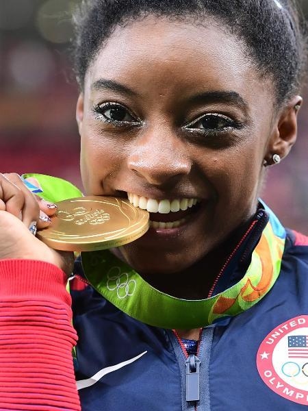 Simone Biles morde a medalha de ouro conquistada em sua apresentação no solo - Emmanuel DUNAND/AFP