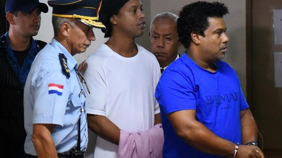 Ronaldinho (branco) e seu irmão, Roberto de Assis Moreira (azul) foram detidos com passaportes falsos no Paraguai - NORBERTO DUARTE/AFP