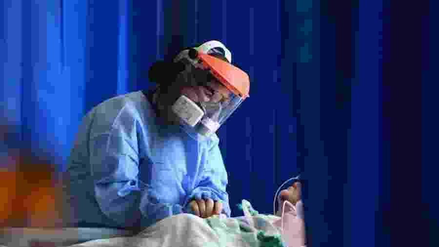 Atendimento a paciente de coronavírus no Brasil -                                 NEIL HALL/POOL/AFP
