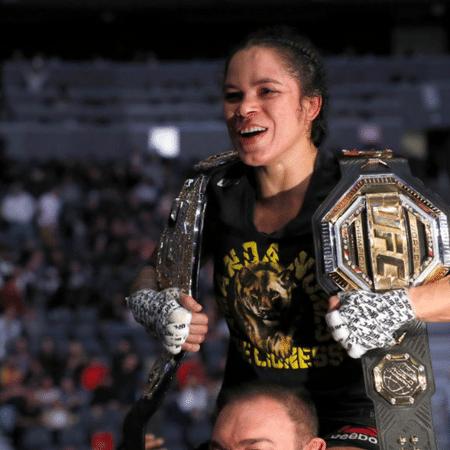 Amanda Nunes comemorando com seus cinturões - GettyImages
