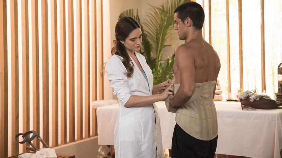 Téo (Felipe Simas) terminando de fazer um exercício, Luna/Fiona (Juliana Paiva) auxiliando. (Divulgação/Globo) - Reprodução / Internet