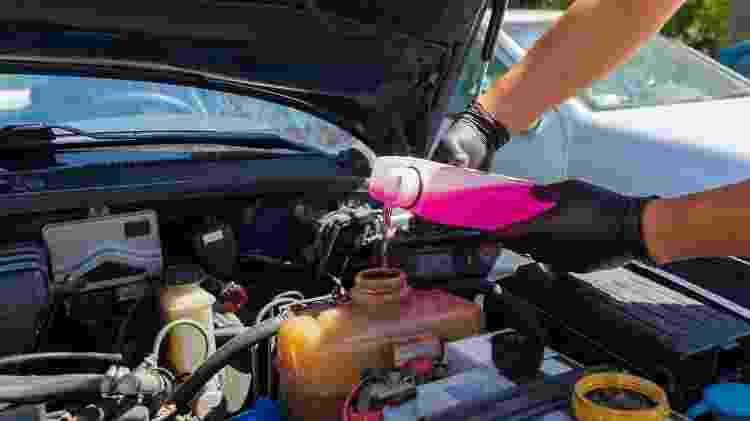 Frentista completando o líquido do radiador do carro com aditivo - Foto: Shutterstock - Foto: Shutterstock