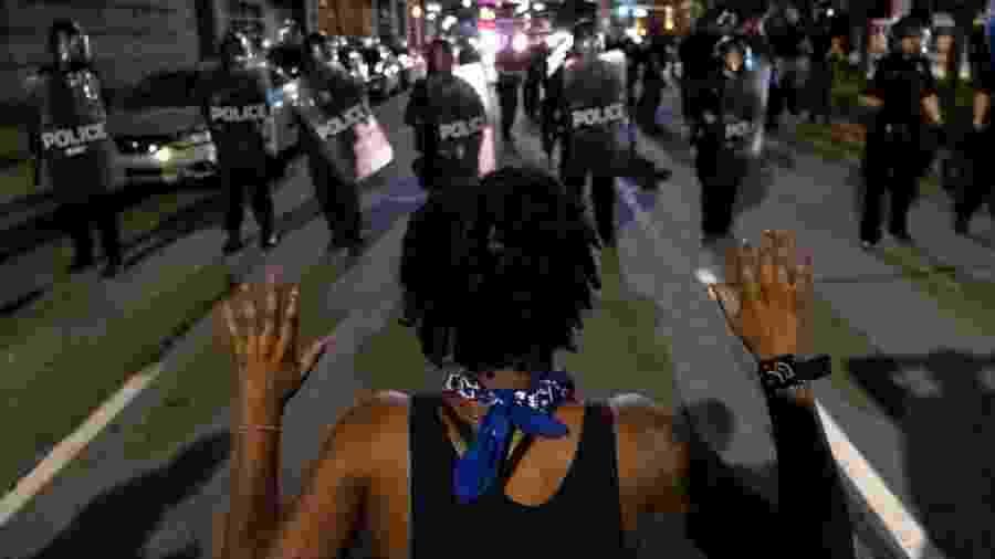 Jovem negro diante de forças de segurança, em protesto contra a violência policial nos Estados Unidos -                                 SETH HERALD/AFP