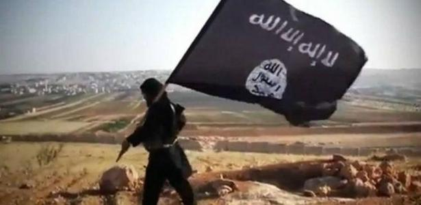 Homem com bandeira do Estado Islâmico