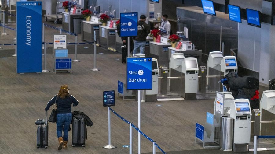 Passageiro usando proteção facial se aproxima da área de check-in do aeroporto de São Francisco, Califórnia, nos EUA - Bloomberg