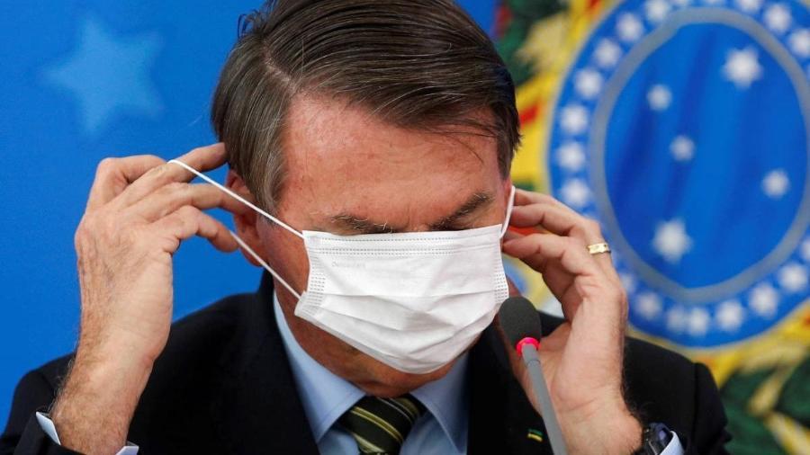 Bolsonaro se atrapalha com máscara - Adriano Machado/Reuters