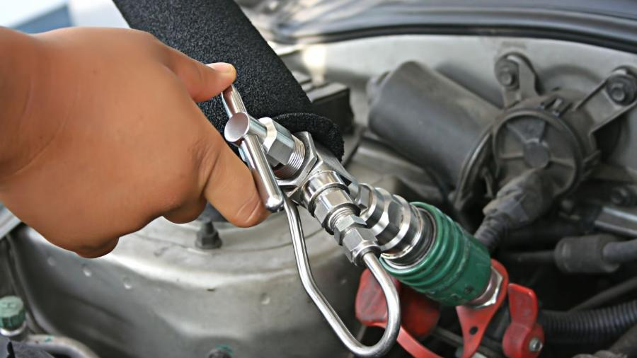Frentista no posto de combustível abastecendo um carro com GNV; busca pela conversão aumentou com alta da gasolina -  Shutterstock