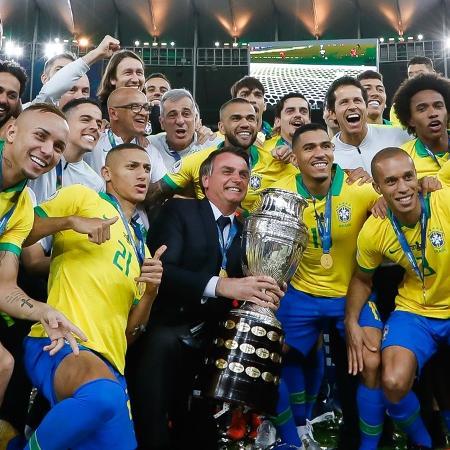 O presidente Jair Bolsonaro posa com a taça da Copa América e a seleção brasileira, no Maracanã, em 2019 (Carolina Antunes/PR) - Reprodução / Internet