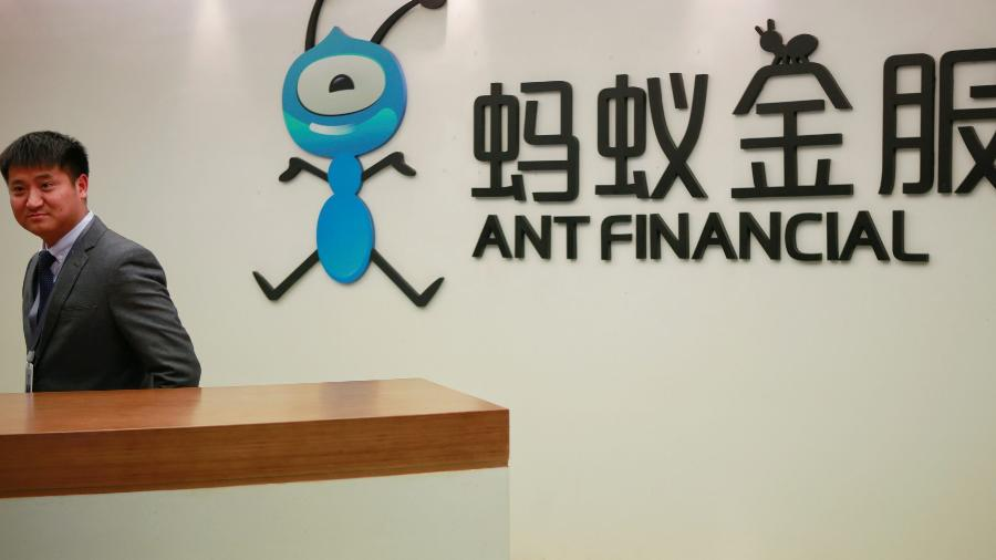 Funcionário ao lado do logotipo da Ant Financial Services Group, fintech da gigante chinesa Alibaba - Shu Zhang/Reuters