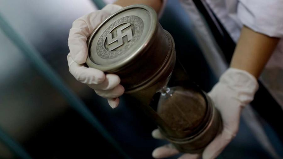 Membro da Polícia Federal segura uma ampulheta com marcas nazistas, na sede da Interpol em Buenos Aires, Argentina - AP Photo/Natacha Pisarenko
