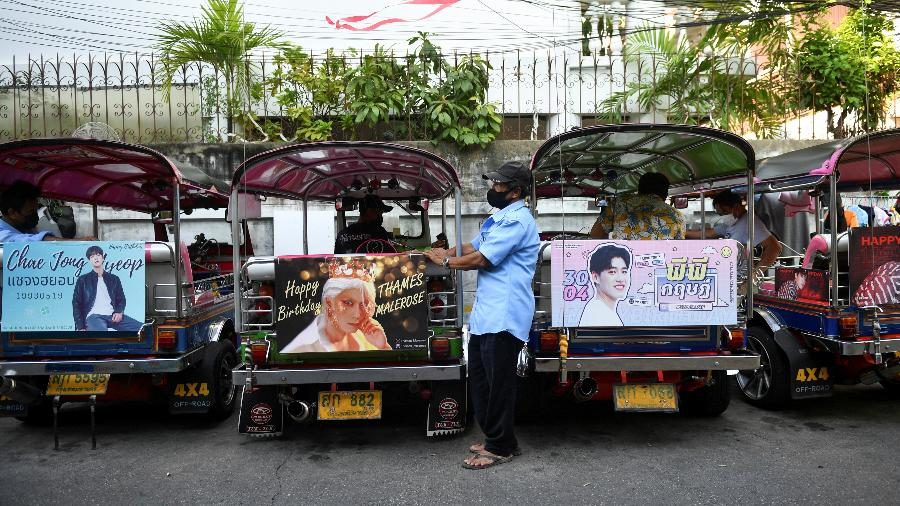 Motorista de tuk-tuk aguarda por clientes, em meio a veículos decorados com banners de astros tailandeses e sul-coranos - REUTERS/Chalinee Thirasupa