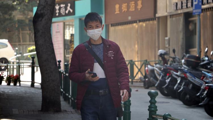 Homem de máscara cirúrgica caminha pelas ruas de Macau, província chinesa - Macau Photo Agency/Unsplash