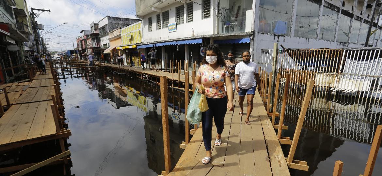 Pessoas caminham sobre pontes de madeira improvisadas em área comercial, no centro de Manaus, devido à cheia do Rio Negro - Nelson Antoine/Folhapress