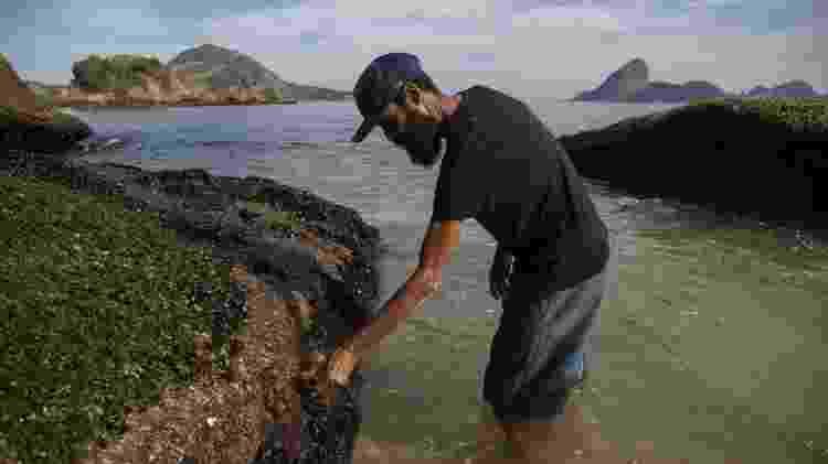 Cláudio Marsel (de camisa preta) cata mexilhões perto da caverna em que mora há mais de oito anos, embaixo do MAC-Niterói - Ricardo Borges/UOL - Ricardo Borges/UOL