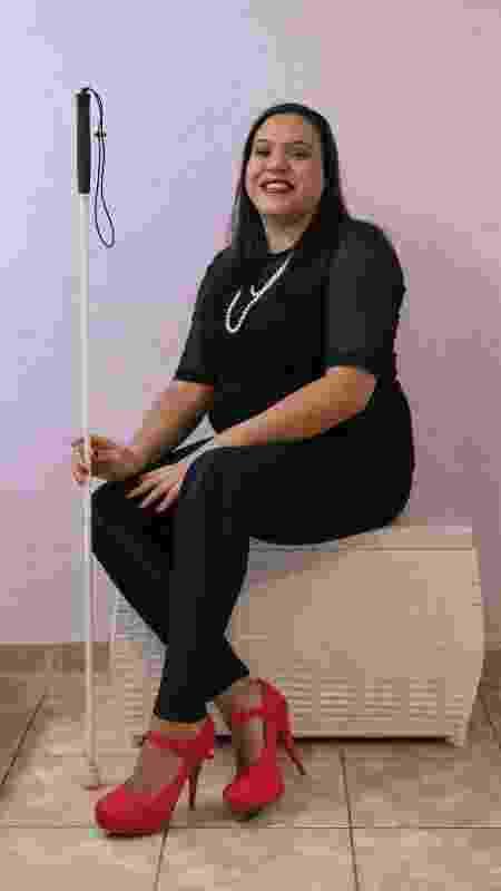 Thaís Coutinho, 31, ficou cega aos 28 anos depois de um AVC hemorrágico. Na foto, está sentada em um banquinho branco segurando sua bengala com a mão direita. Veste blusa e calça preta, um colar de pérolas e sapatos de salto alto vermelhos - Pryscilla K./UOL - Pryscilla K./UOL