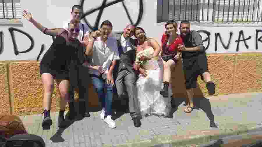 A brasileira Ligia (de vestido branco) e Rafael (de terno cinza) ao lado de amigos após se casarem. Rafael morreu por causa da covid-19 em 22 de março - Arquivo pessoal