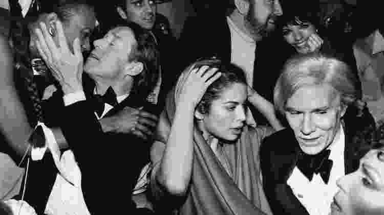 """Andy Warhol em festa de Ano Novo em Nova York, 1978. """"No final dos anos 70, todos queriam festejar no Studio 54 de Nova York. E nessa foto é como se uma velha pintura de mestre ganhasse vida quando ela captura perfeitamente Warhol, Halston, Bianca Jagger, Liza Minelli e amigos"""", diz Bob Ahern - Robin Platzer/Getty Images"""