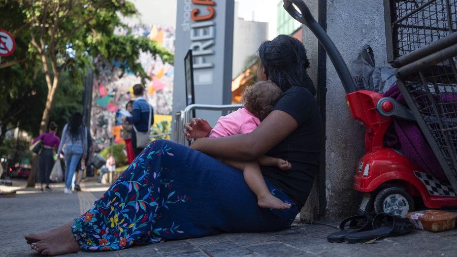 A adolescente G.O.S., 15, pede esmola com a irmã ao colo diante de shopping center em São Paulo - André Porto/UOL