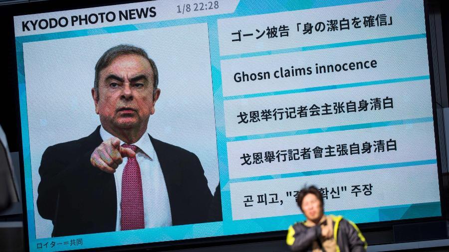 Pedestre passa por outdoor com imagem de Carlos Ghosn, em Tóquio - Behrouz Mehri/AFP