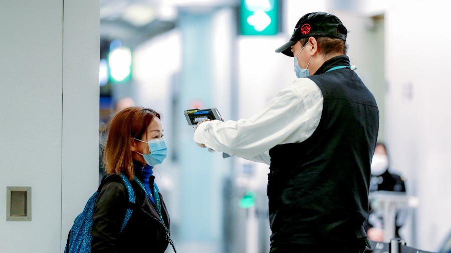 20 fev. 2020 - Trabalhador checa temperatura de passageira no Aeroporto Internacional de Hong Kong - May James/LightRocket via Getty Images