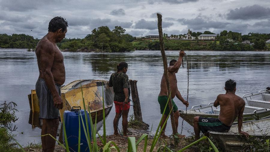 Moradores da comunidade de Santa Maria tentam desvirar uma embarcação no rio Uaupés, na comunidade indígena de São Gabriel da Cachoeira (PA) - Lalo de Almeida/Folhapress