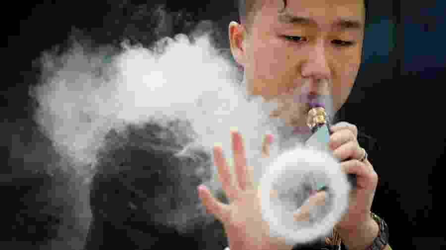 Promotor faz figuras com o vapor de e-cigarro em exposição em Pequim (China) - AFP