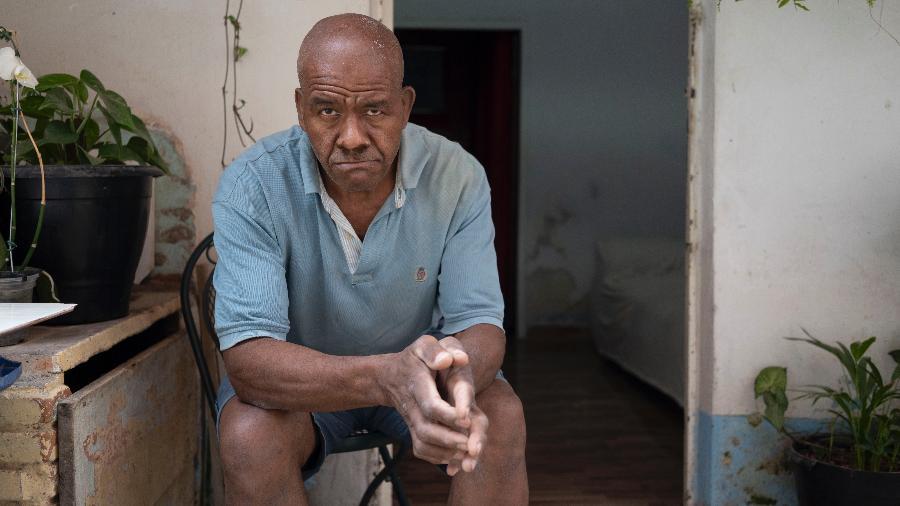 Sem máscara, o aposentado João Mateus Correia posa diante de sua casa em Paraisópolis  - André Porto/UOL