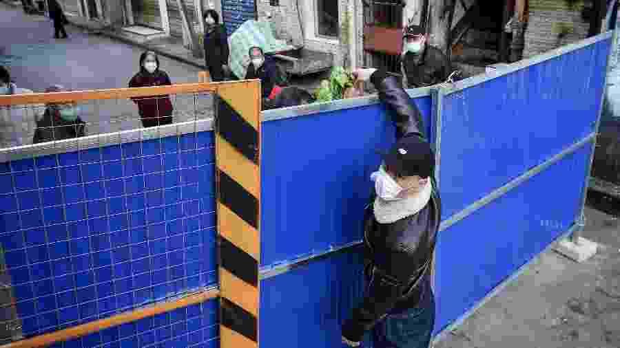 Entregador passa alimentos por cima de barreira em bairro de quarentena em Wuhan, epicentro do surto de coronavírus na China - AFP