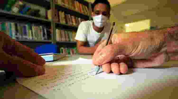 O detento Rodrigo Antônio Monteiro escreve carta de Júnior Soares da Silva, endereçada à tia, Petrúcia, que mora no interior da Paraíba - Marcus Antonius/UOL - Marcus Antonius/UOL