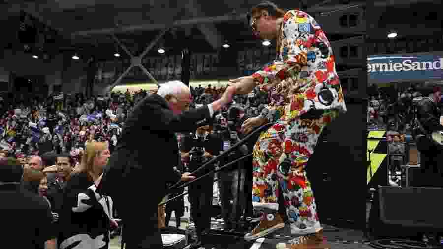 Julian Casablancas, vocalista da banda Strokes, ajuda o pré-candidato democrata Bernie Sanders a subir no palco de comício - Joe Raedle/AFP