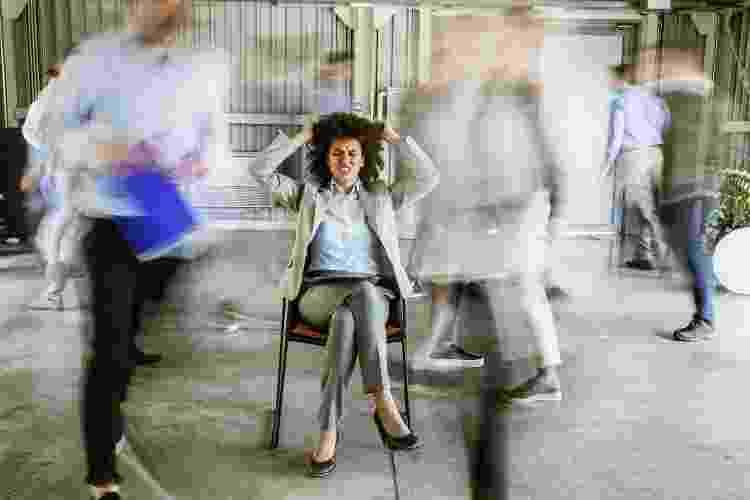 Estresse e burnout: mulher rodeada de colegas, em desfoque - Getty Images - Getty Images