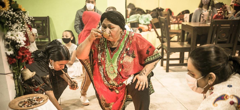 A mãe de santo Mary Pereira bebe vinho de jurema diante de altar para Mestre Malunguinho, guia dos juremeiros - Keiny Andrade/UOL