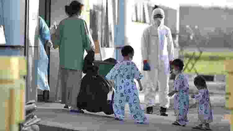 Crianças entram em quarentena após chegarem no aeroporto de Kuala Lumpur, na Malásia - Muzzafar Kasim/Reuters - Muzzafar Kasim/Reuters