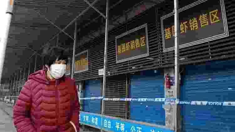 Pedestre passa ao lado do mercado de mariscos de Wuhan, fechado por causa da pandemia de covid-19 - Creative Commons - Creative Commons