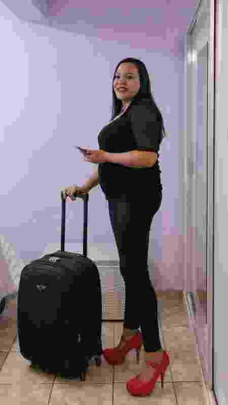 Thaís Coutinho segura uma mala de rodinha na mão direita e o celular na mão esquerda - Pryscilla K./UOL - Pryscilla K./UOL