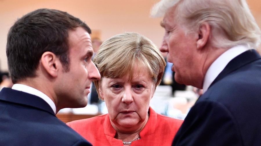 Os líderes Emmanuel Macron (França), Donald Trump (EUA) e Angela Merkel (Alemanha) - John MacDougall/AFP