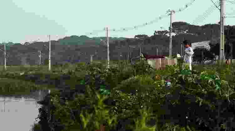 Criança observa o Rio Iguaçu, na Vila Pantanal, em Curitiba - Amanda Andrade/UOL - Amanda Andrade/UOL