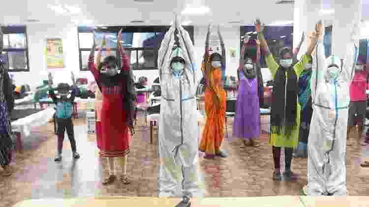 Profissionais de saúde paramentados com EPIs dão aula de yoga a pacientes com Covid em Nova Délhi, na Índia - Raj K Raj/Hindustan Times/Getty Images - Raj K Raj/Hindustan Times/Getty Images