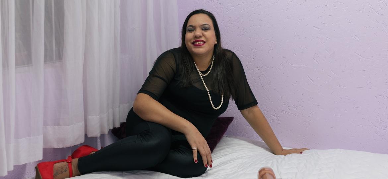 Thaís Coutinho, 31, tem uma sex shop para pessoas cegas. A mulher morena está sentada em uma cama, veste blusa e calça preta e um sapato vermelho. Está maquiada e usa um colar de pérolas. Em sua frente, estão produtos de sex shop: um sutiã vermelho, pérolas e vibradores  - Pryscilla K./UOL