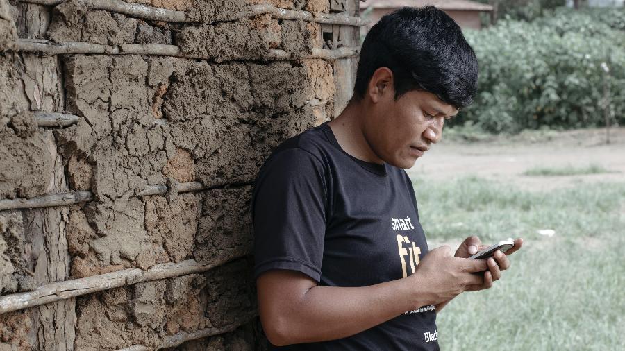 Karai, 24, usa o smartphone para ouvir sucesso de pagode na aldeia Tenondé Porã - Carine Wallauer/UOL