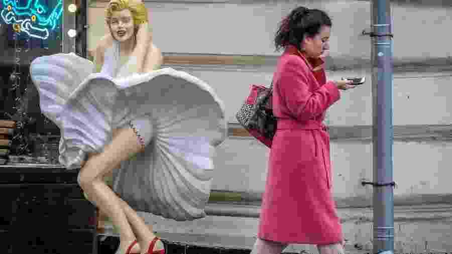 Mulher passa olhando para smartphone e mal percebe estátua de Marilyn Monroe - AFP