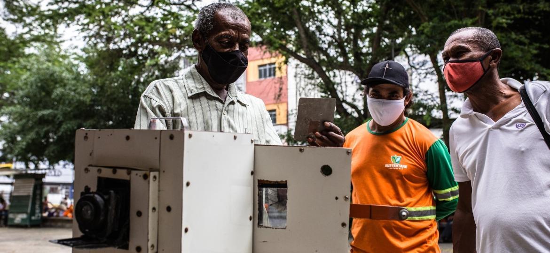 José Alves e José Carlos Assis (de máscara vermelha e camisa branca): os dois lambe-lambes de Feira de Santana (BA) começaram a trabalhar na praça Bernardino Bahia em 1973 - Nelson Oliveira/UOL