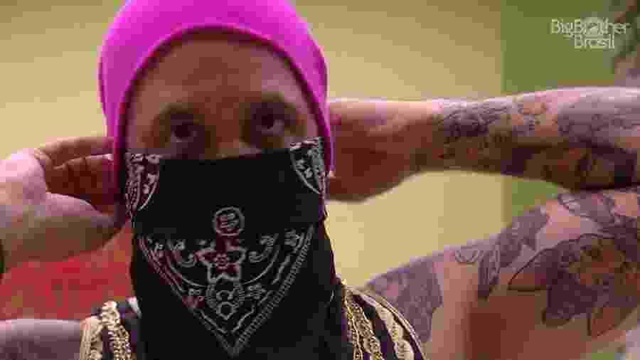 Caruso coloca bandana no rosto ao provar figurino da festa - Reprodução/GloboPlay