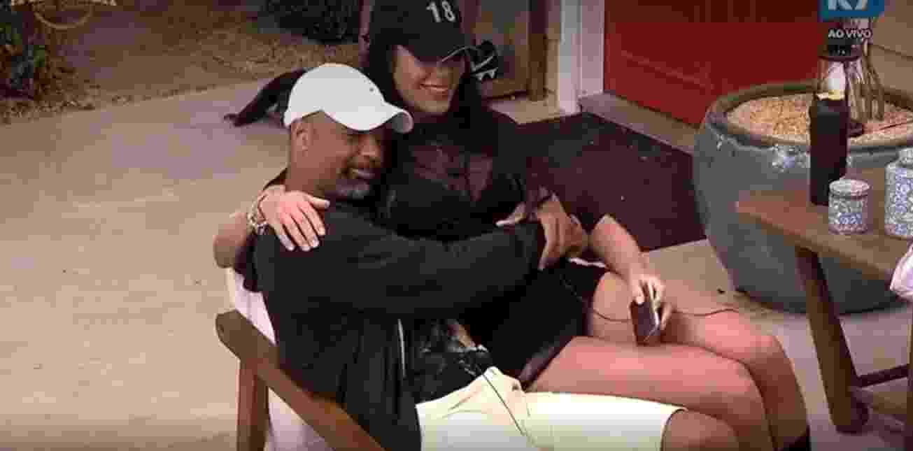 Dinei e Monique se abraçam na área externa - Reprodução/R7