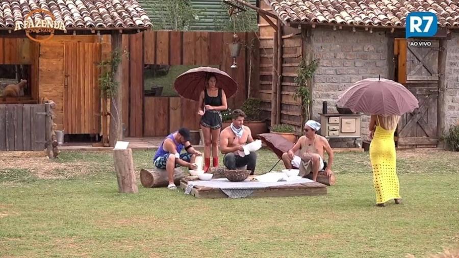 Moradores da baia ralam mandioca embaixo de chuva  - Reprodução/R7