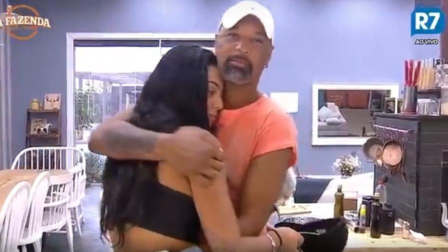 Dinei e Monique se abraçam na sala da casa - Reprodução/R7